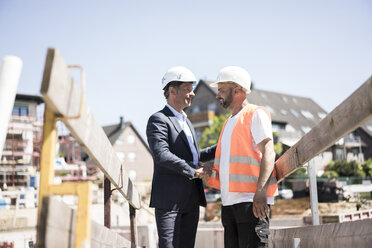 Man in suit shaking hands with construction worker on construction site - MOEF01255