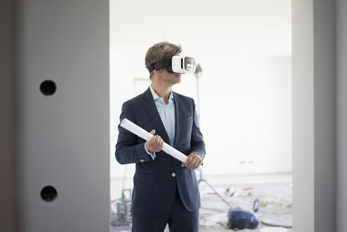 Man in suit wearing VR glasses in building under construction - MOEF01279