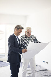 Happy man in suit and senior man looking at blueprint - MOEF01282