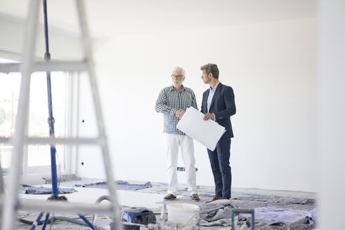 Man in suit and senior man talking on room under construction - MOEF01285