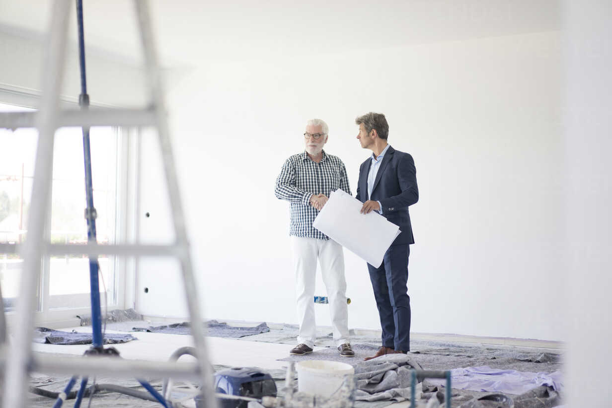 Man in suit and senior man talking on room under construction - MOEF01285 - Robijn Page/Westend61