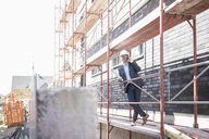 Architect on cell phone on scaffolding on construction site - MOEF01288