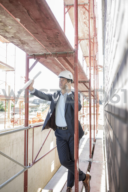 Architect on cell phone on scaffolding on construction site - MOEF01291 - Robijn Page/Westend61