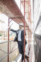 Architect on cell phone on scaffolding on construction site - MOEF01291