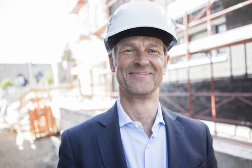Portrait of confident architect wearing hard hat on construction site - MOEF01294
