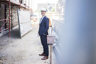 Smiling architect wearing hard hat standing on construction site - MOEF01297