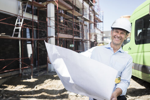 Portrait of smiling architect with blueprint wearing hard hat on construction site - MOEF01300
