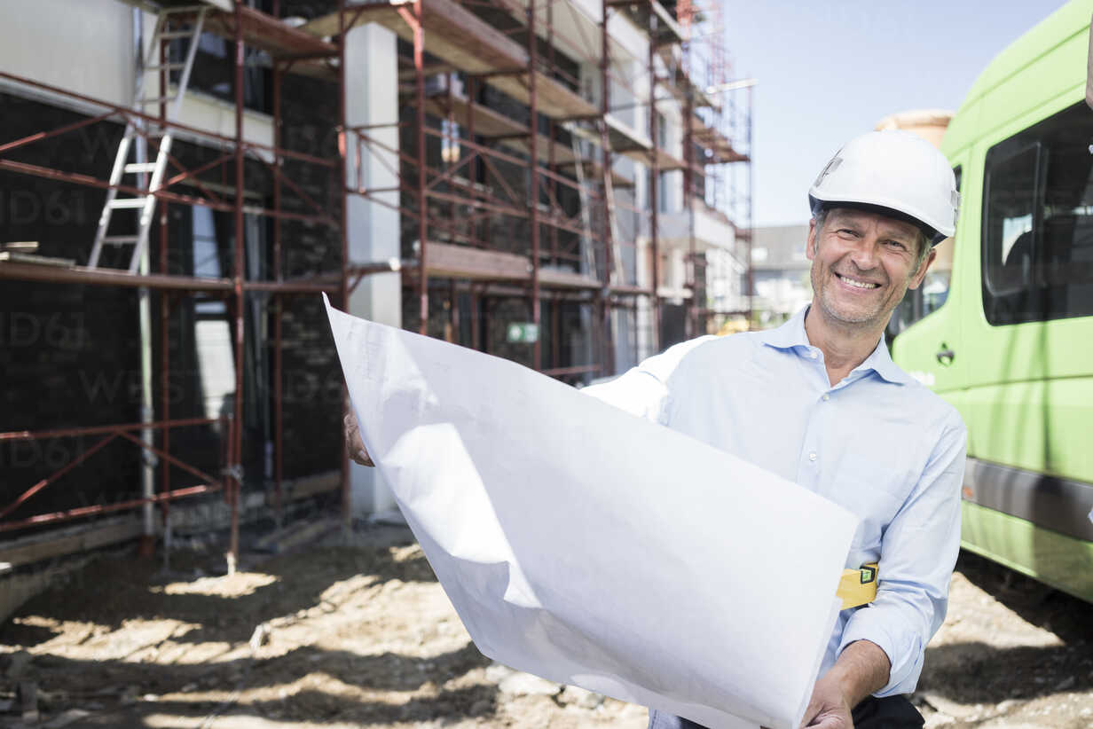 Portrait of smiling architect with blueprint wearing hard hat on construction site - MOEF01300 - Robijn Page/Westend61