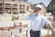 Man wearing hard hat on cell phone on construction site - MOEF01306
