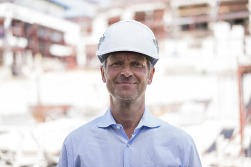 Portrait of confident man wearing hard hat on construction site - MOEF01312