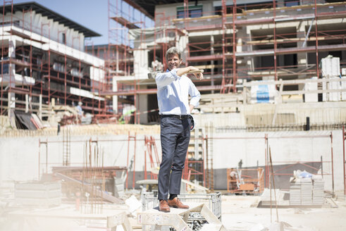 Smiling man standing on construction site holding a hammer - MOEF01315