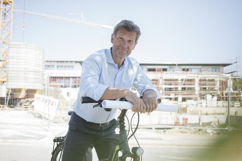 Portrait of man with e-bike on construction site - MOEF01321