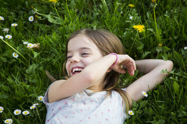 Portrait of laughing little girl lying on a meadow - LVF07032