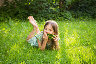Portrait of little girl lying on a meadow eating watermelon - LVF07035