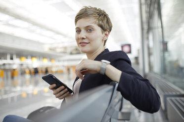 Portrait of blond businesswoman using smartphone - PNEF00687