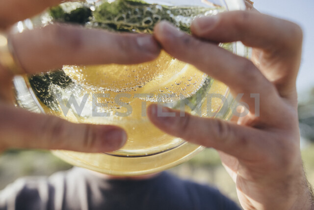 Detail of man drinking water infused with lemon and mint - KMKF00288