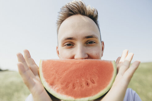 Portrait of a young man holding a watermelon outdoors - KMKF00294
