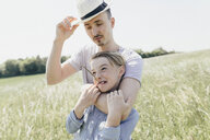 Young man wearing hat and boy on a field - KMKF00300