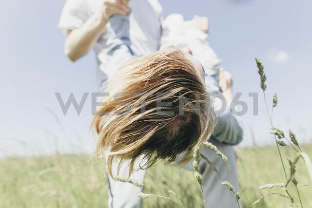 Man carrying happy boy in a field - KMKF00306