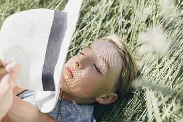Boy with a hat lying in field - KMKF00312