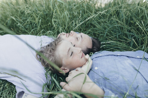Young man and boy lying in field - KMKF00315