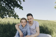 Portrait of young man embracing boy at a field - KMKF00318