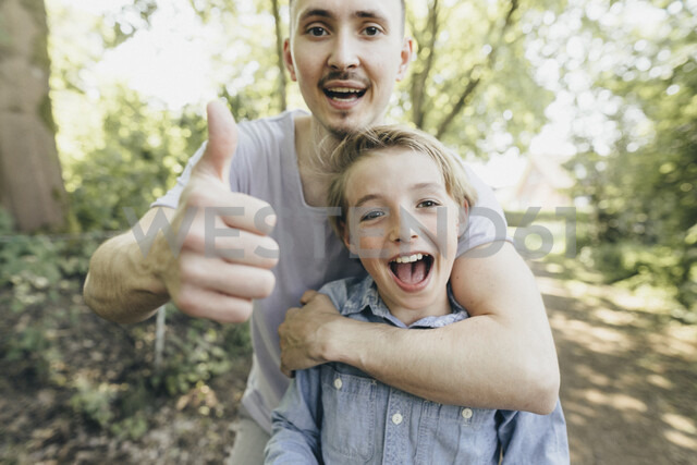 Portrait of happy young man embracing boy on forest path - KMKF00324 - Katharina Mikhrin/Westend61