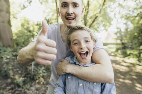Portrait of happy young man embracing boy on forest path - KMKF00324