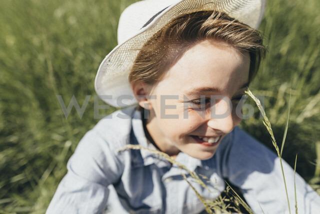 Happy boy wearing a hat sitting in field - KMKF00339