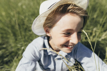 Happy boy wearing a hat sitting in field - KMKF00339
