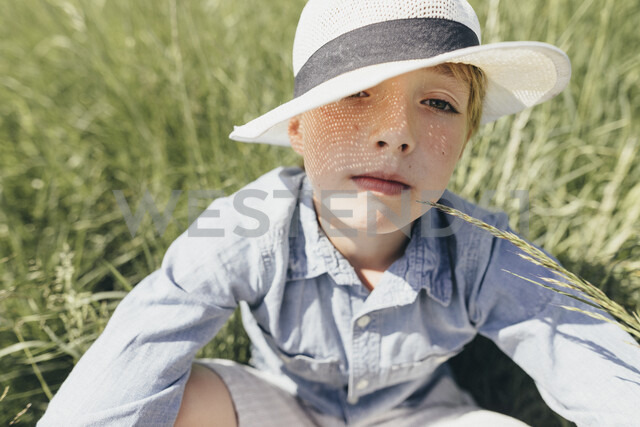 Portrait of boy wearing a hat sitting in field - KMKF00342