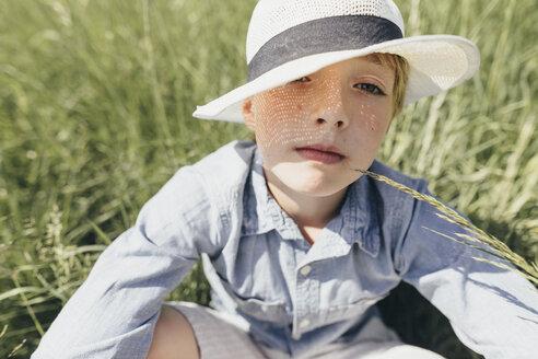 Portrait of boy wearing a hat sitting in field - KMKF00342