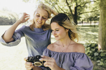 Two smiling young women with old-fashioned camera in a park - KMKF00350