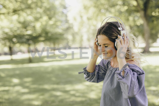 Smiling young woman in a park enjoying listening to music with headphones - KMKF00356 - Katharina Mikhrin/Westend61