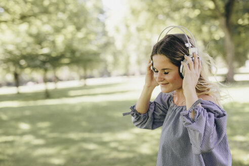 Smiling young woman in a park enjoying listening to music with headphones - KMKF00356