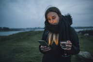 France, Brittany, Landeda, young woman with cell phone and glass of wine at the coast at dusk - GUSF00943