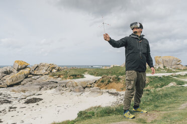 France, Brittany, Meneham, man with miniature wind turbine wearing VR glasses at the coast - GUSF00946