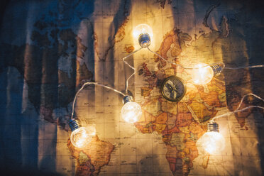 Compass and fairy lights on world map - GUS00949