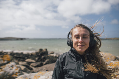 France, Brittany, Landeda, smiling young woman wearing headphones at the coast - GUSF00955