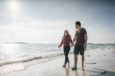 France, Brittany, Landeda, couple walking hand in hand on the beach - GUSF00964