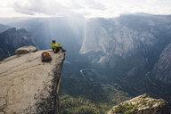 Man sitting at top of mountain, overlooking Yosemite National Park, California, USA - ISF08833