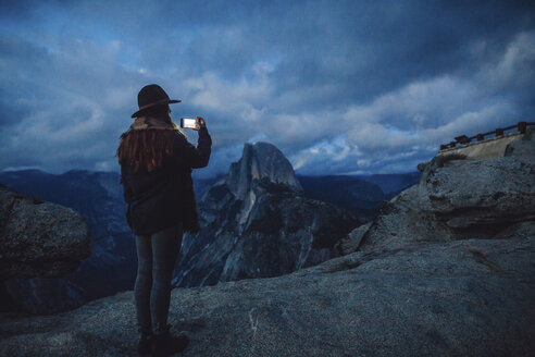 Young woman taking photograph on rock overlooking Yosemite National Park at dusk, California, USA - ISF08836