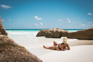 Mid adult woman in bikini relaxing at beach against blue sky during sunny day, Seychelles - FSIF03018