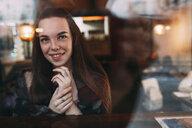 Smiling beautiful young woman seen through cafe window - FSIF03051