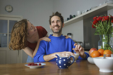 Cheerful mid adult couple at table with breakfast in room - FSIF03066