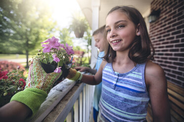 Hand wearing gardening glove handing plant to boy and girl - ISF08902