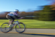 Blurred motion side view of cyclist cycling - ISF08911