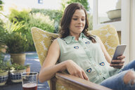 Woman in armchair texting on smartphone - ISF08914