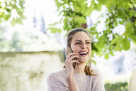 Portrait of laughing woman on the phone outdoors - FMKF05084