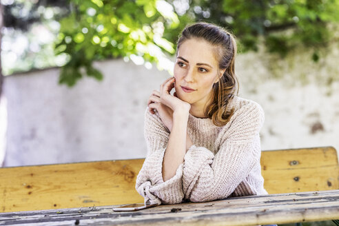 Portrait of pensive woman sitting on bench at courtyard - FMKF05087